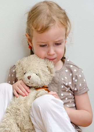Sad lonely little girl sitting with teddy bear near the wall