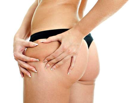 muslos: Joven, mujer, doblando la piel en las caderas con ambas hands.Close encima de la vista. Aislados en blanco Foto de archivo