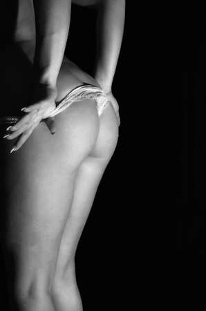 Young slim woman taking off white panties  Close up view  Black and white Stock Photo - 16219817