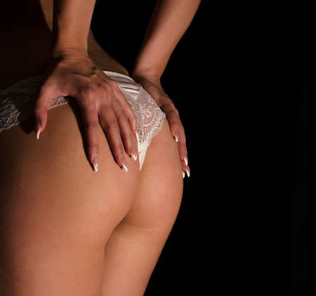 erotic fantasy: Close up view of slim female buttock with both hands on it   Stock Photo