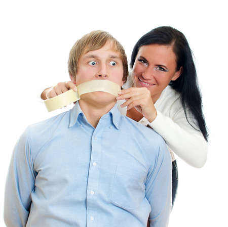 silenced: Woman applying tape on mans mouth. Isolated on white. Stock Photo