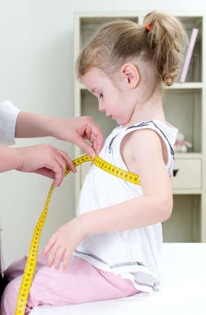 Pediatrician measuring toddler photo