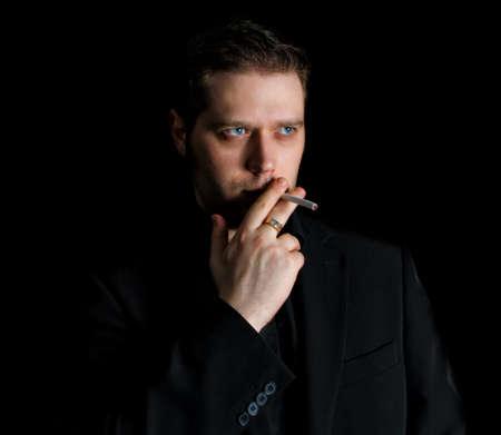 crossed cigarette: Portrait of smoking man in black suit