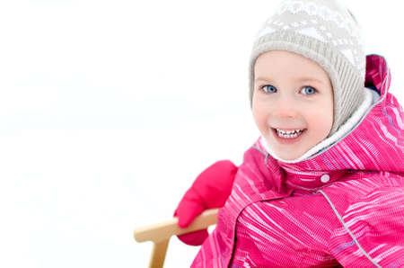 Portrait of cute little girl sitting in sled photo