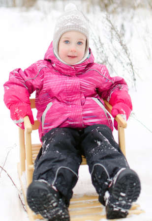Cute little girl sitting in sled in the park photo