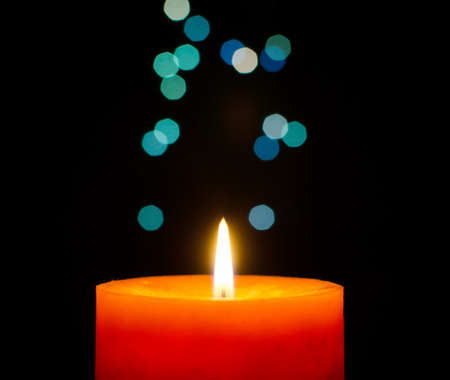 Burning candle on a christmas lights bokeh background photo