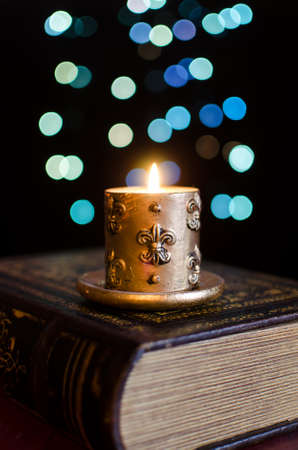 Burning candle and old book on bokeh background photo