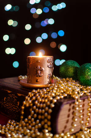 Burning candle and seasonal decorations on bokeh lights background photo