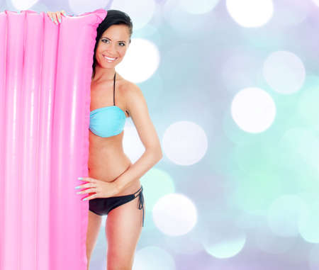 Young woman holding pink inflatable mattress on blue bokeh background Stock Photo - 17038620