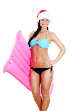 Young woman in bikini and christmas hat holding inflatable mattress. Isolated on white photo