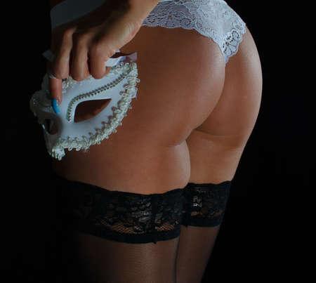 nalga: Sexuales nalgas femeninas en las bragas blancas y brazo que sostiene la m�scara del carnaval