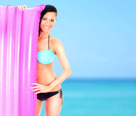 Young woman holding pink inflatable mattress on sea background photo
