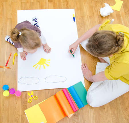 Young woman and little girl drawing together sitting on the floor  Top view