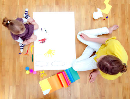 two floors: Young woman and little girl drawing together sitting on the floor  Top view