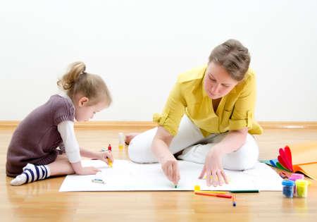 Mujer joven y niña dibujo juntos sentados en el suelo