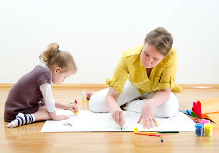 art activity: Young woman and little girl drawing together sitting on the floor Stock Photo