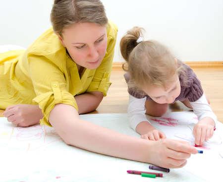 Jeune femme et le dessin petite fille ensemble assis sur le plancher Banque d'images