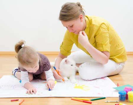 zooth�rapie: Jeune femme et le dessin petite fille ensemble assis sur le plancher