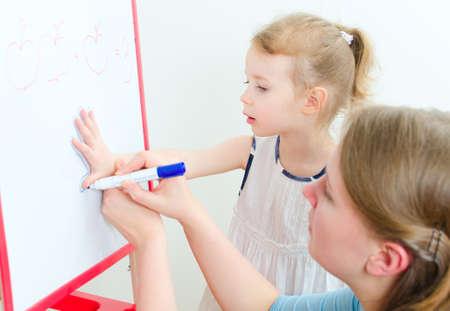 Pretty little girl with teacher near whiteboard photo