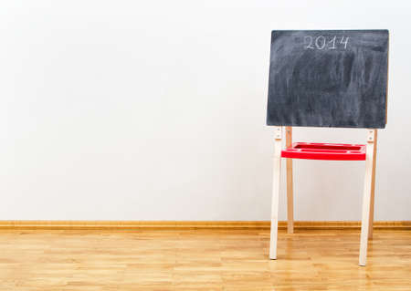 Small blackboard near the wall in empty room photo