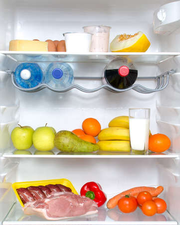 Open fridge full of fruits, vegetables and meat photo