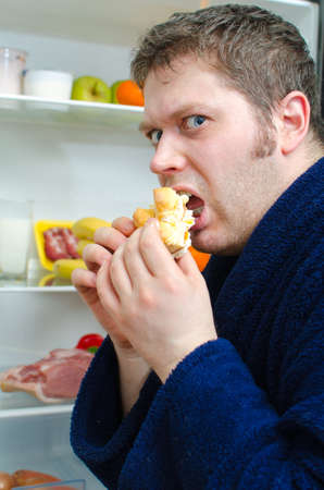 surfeit: Handsome man eating piece of cake near open fridge