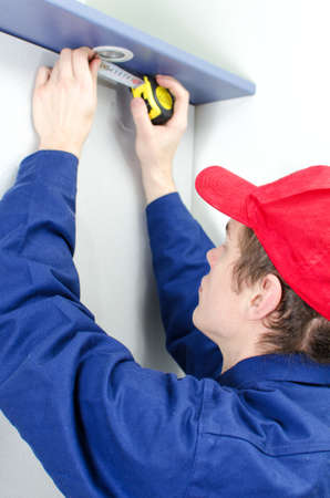 Young tradesman in uniform measuring solid-state lighting Stock Photo - 17842178