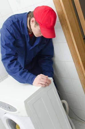 Young worker repairing washing machine photo