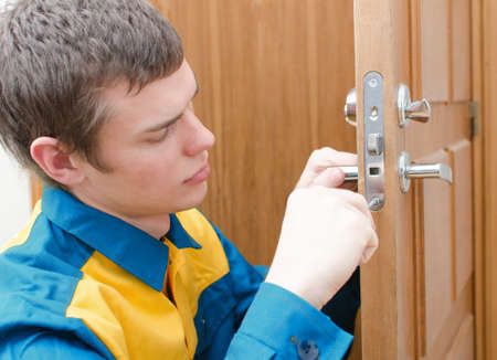 lock: Young handyman in uniform changing door lock