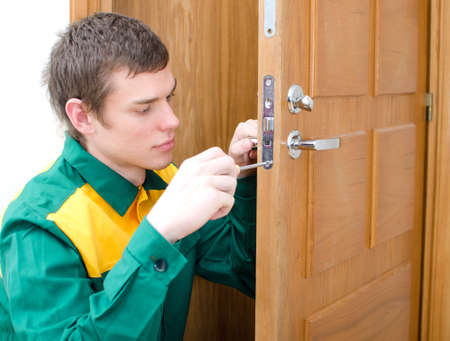 Young handyman in uniform changing door lock photo