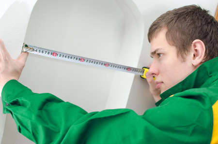 Young handyman in uniform working with measure tape photo