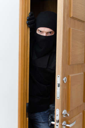 robberies: Male burglar in mask breaking into the house Stock Photo