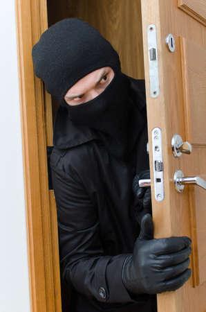 Male burglar in mask breaking into the house Reklamní fotografie