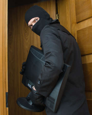 男性泥棒は家に侵入し、モニターを盗んでマスクで 写真素材