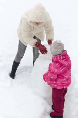 Mother and child making snowman  photo