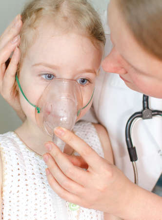 Doctor helps little girl to do inhalation photo