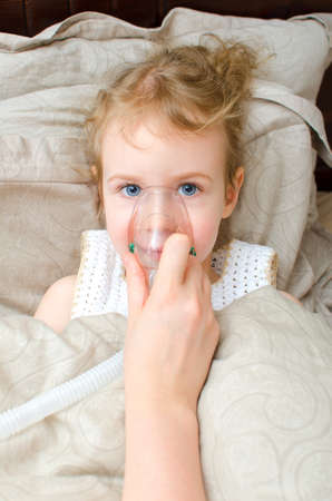 Portrait of little girl lying in bed with inhalator mask on the face photo