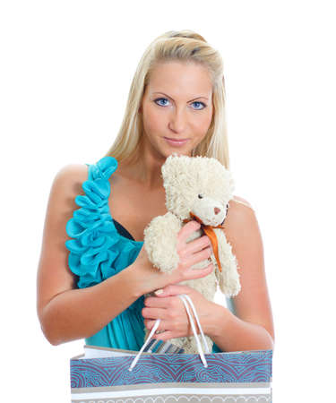 Young pretty woman with teddy bear and shop bag. Isolated on white photo