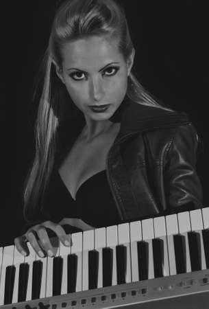 Sexy lady in bra and leather coat posing with synthesizer  Black and white photo