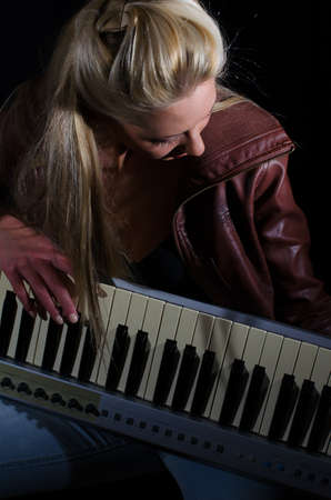 Sexy lady in bra and leather coat posing with synthesizer over black background photo