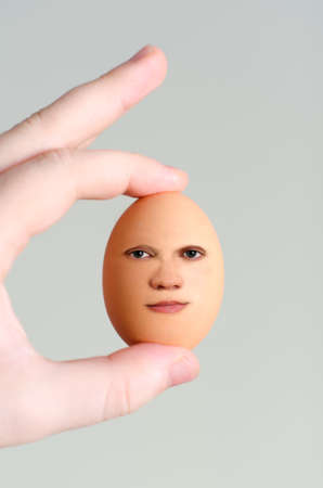 Male hand holding egg with human face Stock Photo - 18063059