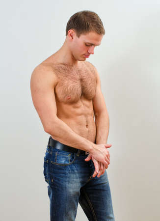 naked male body: Young handsome guy in jeans with bare torso against the wall Stock Photo