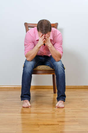 Depressed man sitting on a chair against the wall photo