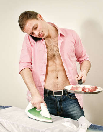 workless: Young man with pan and phone ironing his shirt