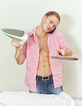workless: Young man with pan and iron speaking on the phone Stock Photo