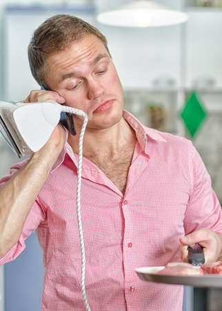 workless: Young man with pan and iron speaking on the phone on kitchen background