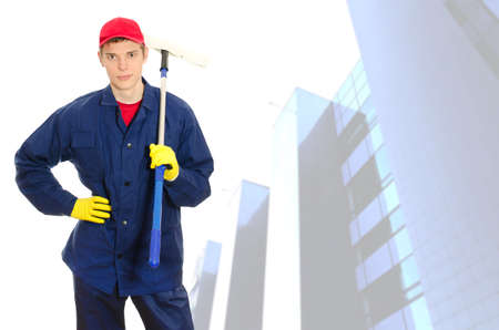 Young male window cleaner with wiper over building with glass facade photo