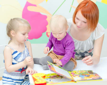 babysitter: Mother and her daughters reading a book Stock Photo