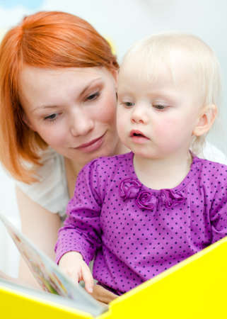 Mother and her daughter reading a book Stock Photo