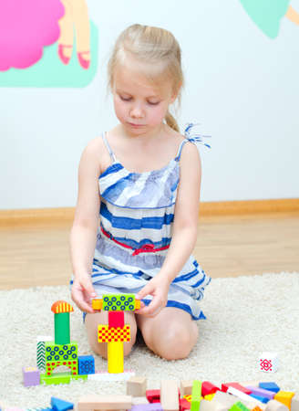 Cute little girl sitting on the floor and playing with building blocks photo
